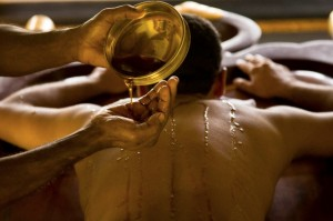 India - Ayurveda - A masseur pours warm oil over a patients body to prepare him for massage
